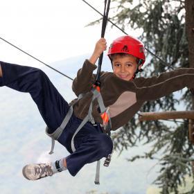 Immagine di un bambino che si diverte su un percorso avventura tra gli alberi